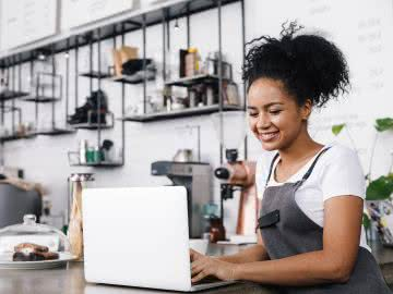 Young cafe owner researching her business growth fund options