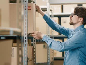 Warehouse working restocks the shelves using Amazon lending