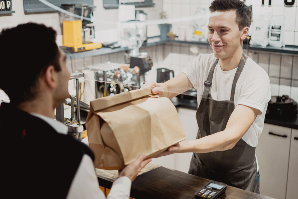 Buys lunch pizza and pasta in a paper bag with a takeaway. small business pizzeria coffee shop. a young male employee picks up dinner. convenient delivery in a corrugated cardboard box.