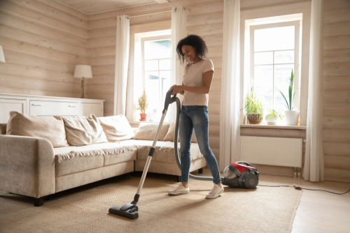 Happy african American young woman preform household chores cleaning living room using modern vacuum cleaner, smiling biracial wife hoover remove dust from home carpet, do housekeeping job