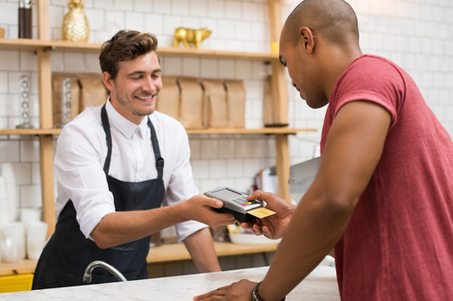 A server holds a credit card reader while a Black customer pays by credit card.
