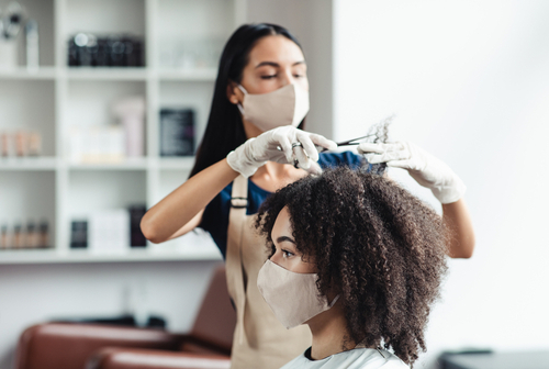 Hairdresser with security measures for Covid-19, cutting hair of woman with medical mask at beauty salon