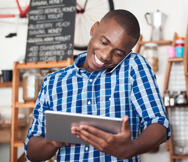 Smiling young African entrepreneur talking on a cellphone and using a digital tablet while standing at the counter of his cafe
