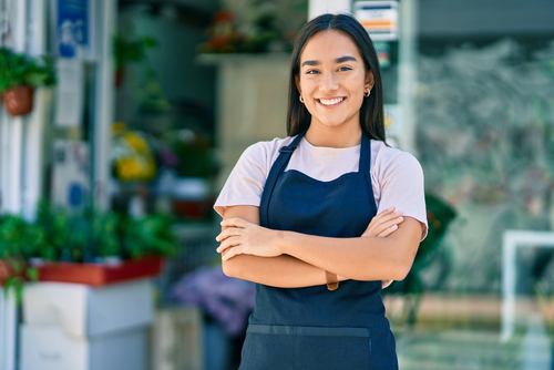 Young latin shopkeeper girl with arms crossed smiling happy standing at the florist