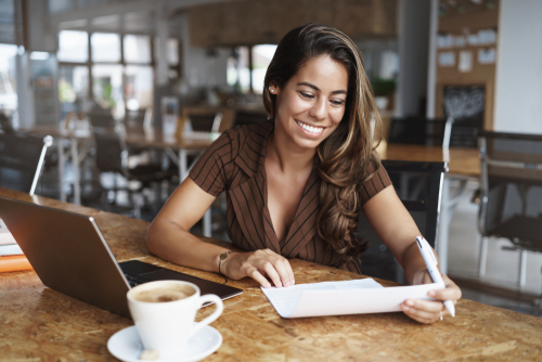 Happy attractive smiling latino woman sitting cafe, co-working urban space, grining delighted, reading paper and make corrections, prepare for office meeting, sit near opened laptop drink cappuccino